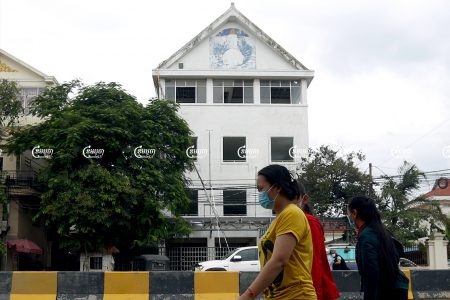Pedestrians walk past the former Cambodia National Rescue Party headquarters in Phnom Penh. Picture taken on May 24, 2021. CamboJA/ Pring Samrang