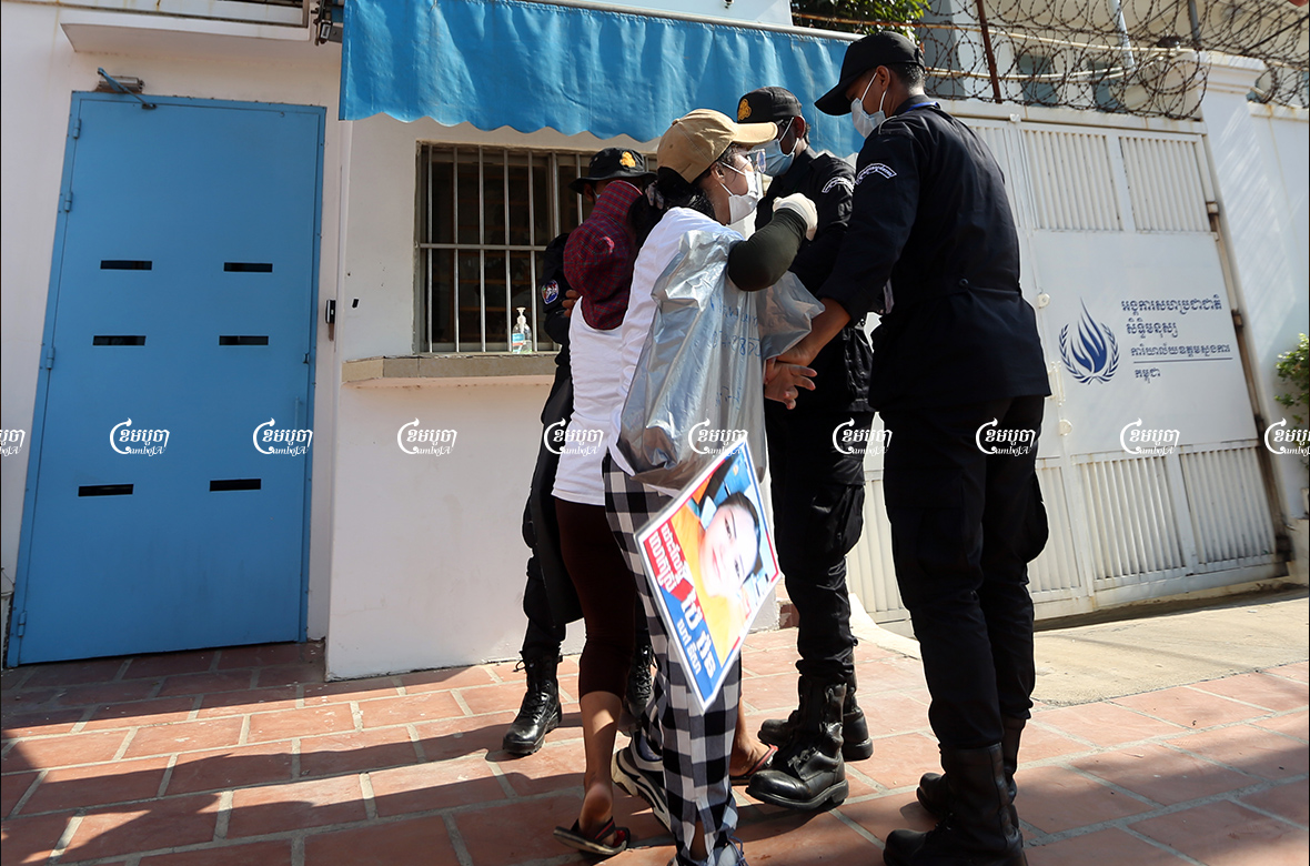 Security personnel seize banners from relatives of imprisoned CNRP members at a small demonstration. Protestors had submitted a petition to a UN office in Phnom Penh seeking help in freeing their family members, June 4, 2021. CamboJA/ Pring Samrang
