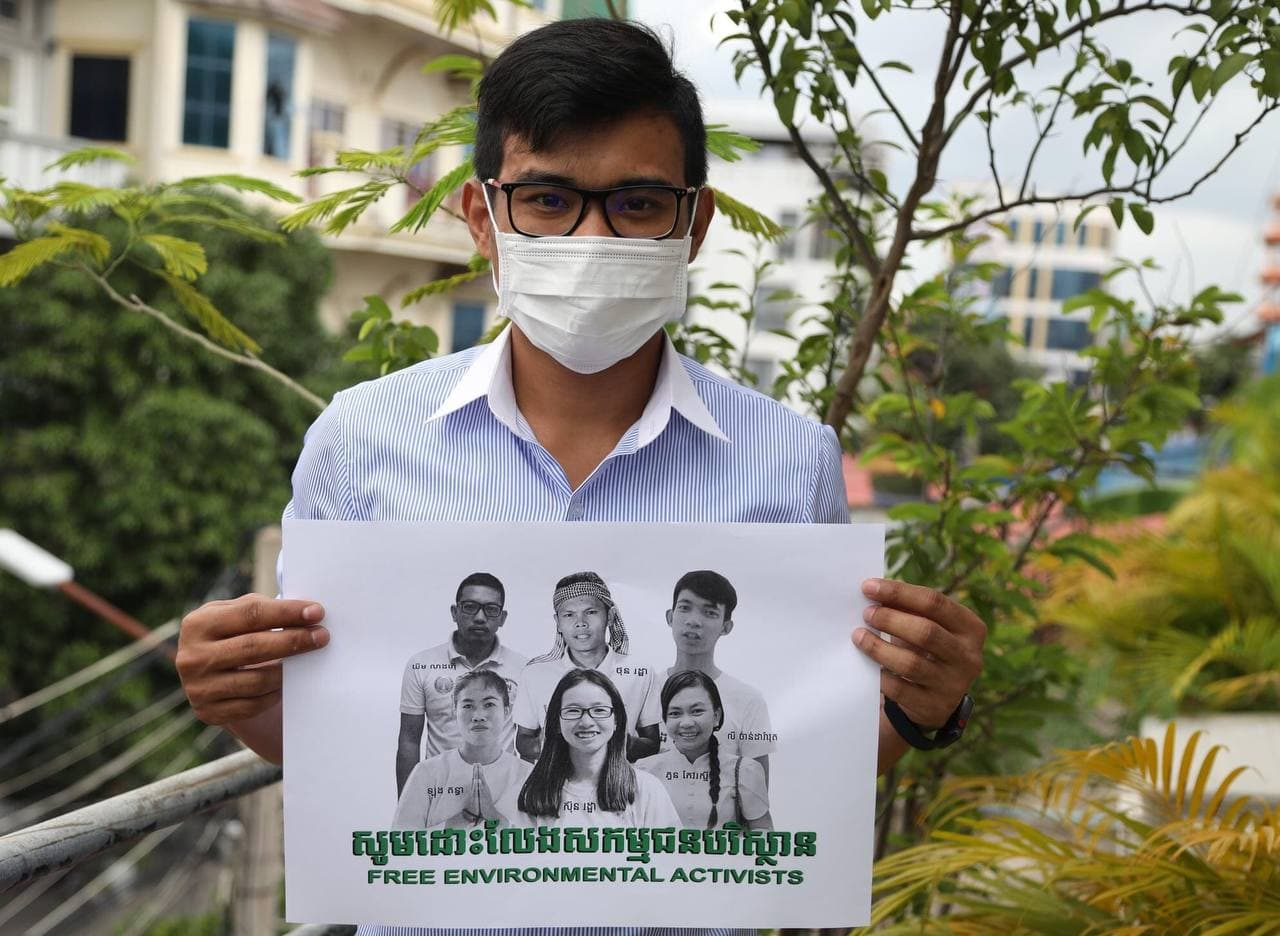 An NGO staff member holds up a photo of imprisoned Mother Nature environmental activists as part of a social media campaign calling for the six youths' release.