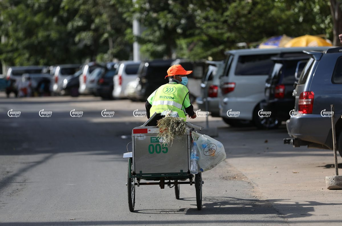 A Mizuda Group worker collects garbage along a street in Chaktomuk commune, Daun Penh district, August 17, 2021. CamboJA/ Pring Samrang