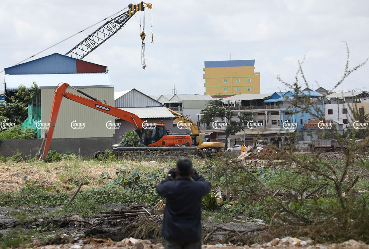 A man uses a smartphone to take photos Friday as local authorities use excavators to demolish homes in the Boeng Tompun 1 commune in the Meanchey district of Phnom Penh. Photo taken August 13, 2021. CamboJA/ Pring Samrang