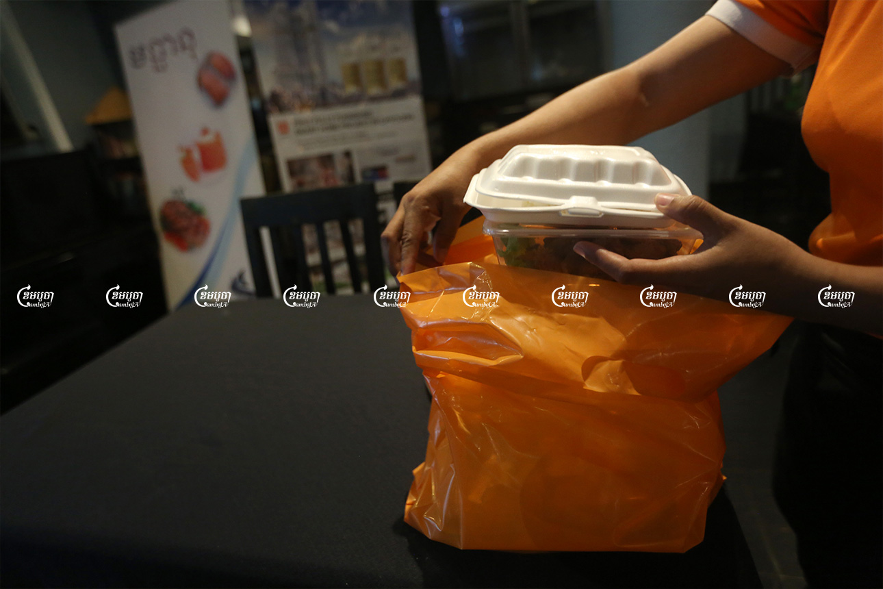 A staff member packs food for a customer at a restaurant in Phnom Penh, August 10, 2021. CamboJA/ Pring Samrang