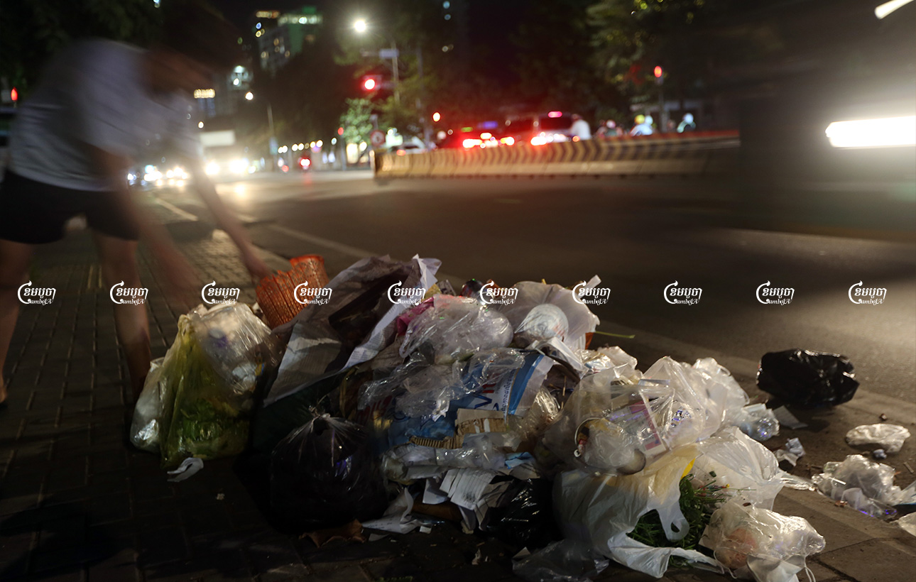 A teenager drops plastic bags filled with trash along a street in Phnom Penh, August 10, 2021. CamboJA/ Pring Samrang