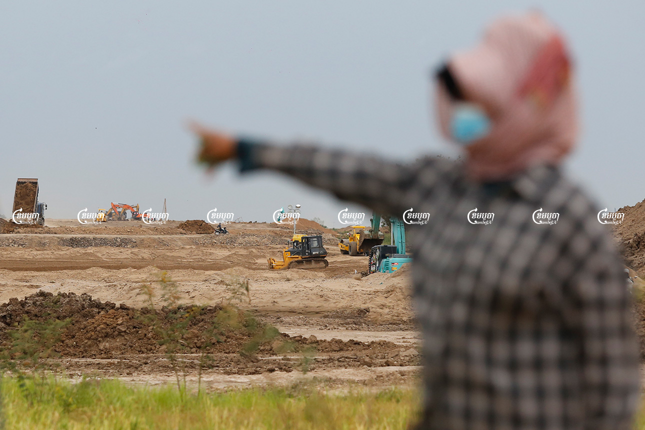 A villager looks on as construction crews use excavators and bulldozers to prepare land for the massive new airport in Kandal province. Picture taken on July 29, 2021. CamboJA/ Panha Chhorpoan