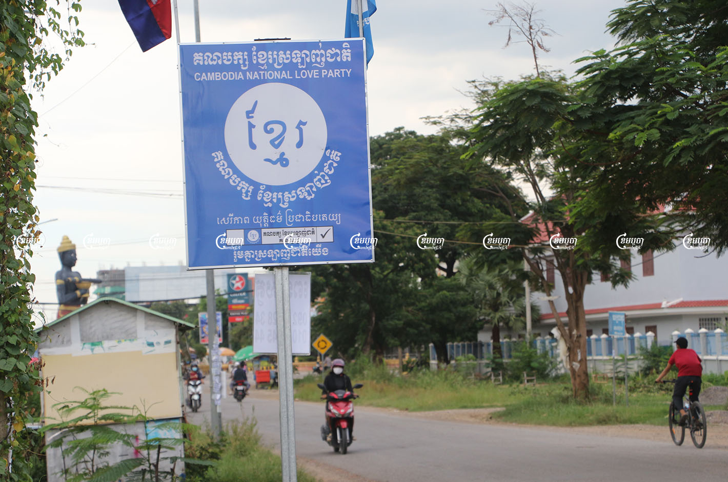 Drivers pass a sign for the newly formed Cambodia National Love Party in Battambang city. Photo taken on August 17, 2021. CamboJA/ Panha Chhorpoan