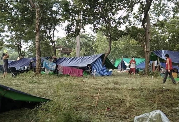 Returning migrant workers have built temporary shelters from tarps in the forest near the Thai-Cambodian border. Supplied