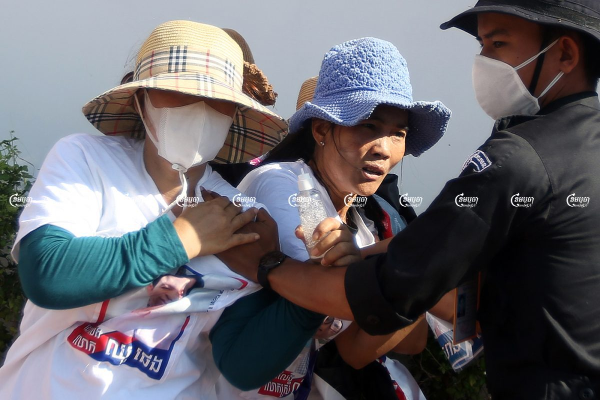 Security personnel seize banners from relatives of imprisoned CNRP members at a small demonstration. Protestors had submitted a petition to a UN office in Phnom Penh seeking help in freeing their family members, Picture taken on June 4, 2021. CamboJA/ Pring Samrang