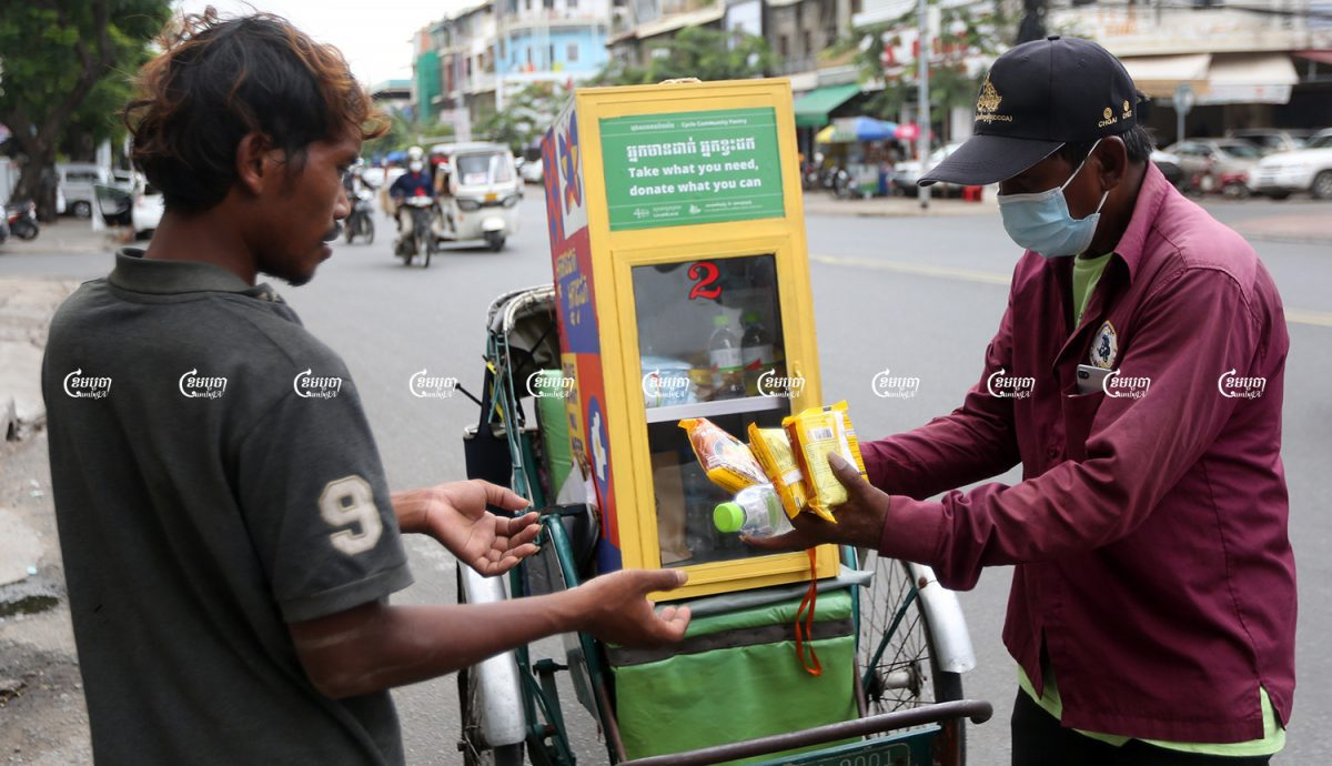 A cyclo driver offers food from his mobile pantry to a man in Phnom Penh, August 28, 2021. CamboJA/ Pring Samrang