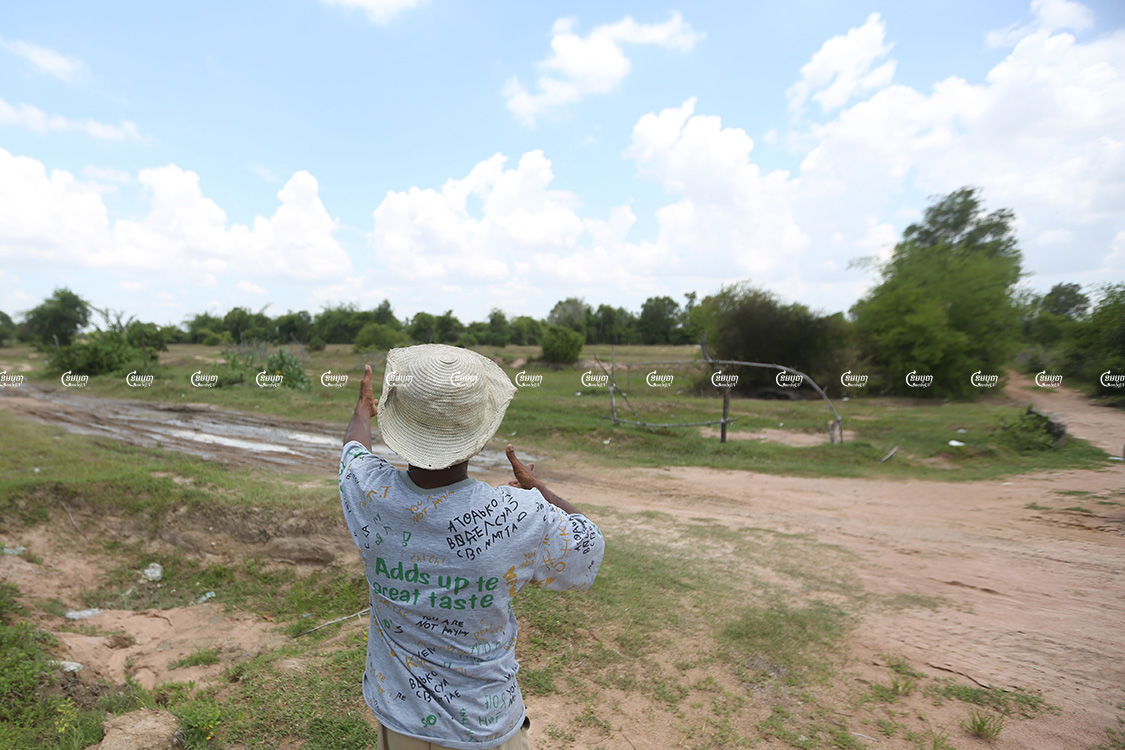 A villager points to a disputed land site in Kandal Province's Ang Snuol district the day after soldiers shot and injured one villager trying to prevent armed forces from closing off the road. Picture taken June 4, 2021. CamboJA/ Pring Samrang