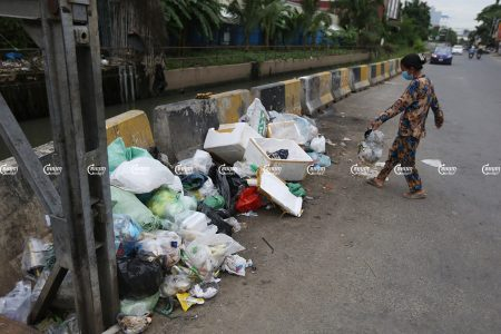 A woman drops garbage on a trash pile on a street in Phnom Penh, September 23, 2021. CamboJA/ Pring Samrang