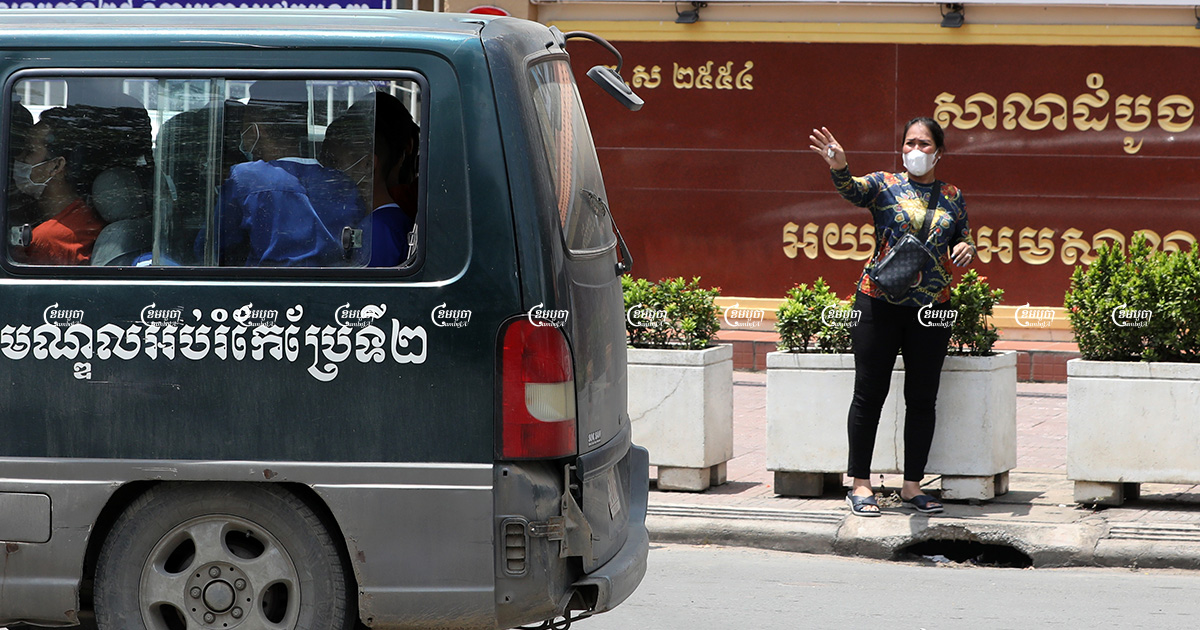 Kak Sovann Chhay's mother Prum Chantha waves to her son in the prisoner's van in front of the Municipal Court of Phnom Penh after his hearing, September 29, 2021. CamboJA/ Pring Samrang