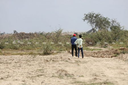 Villagers walk across their plot of land in Kandal province. The plot is part of a large swathe of land that will become the site of a new airport. Picture taken March 2, 2021. CamboJA/ Pring Samrang