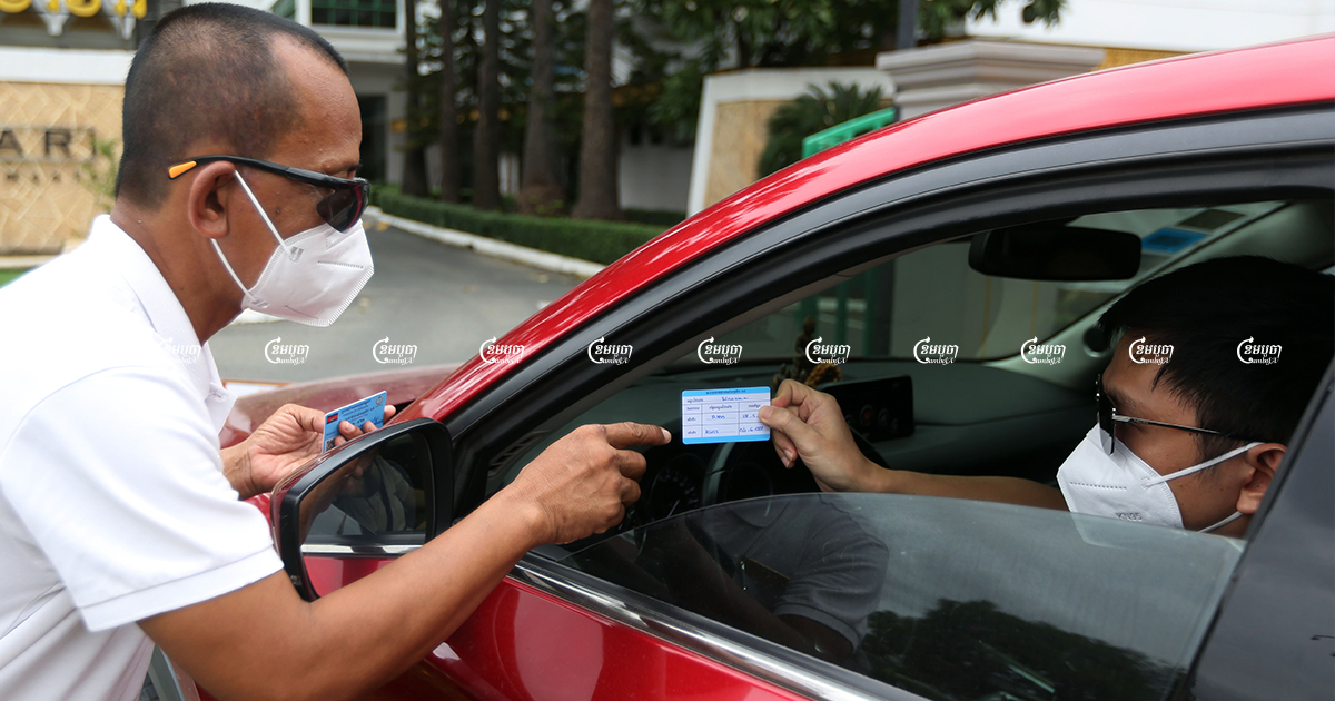 A Phnom Penh hotel security guard checks a costumer's COVID-19 vaccination card before allowing them to enter, October 11, 2021. CamboJA/ Pring Samrang
