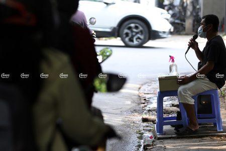 A blind man sings on a street for money in Phnom Penh, Picture taken September 21, 2021. CamboJA/ Pring Samrang
