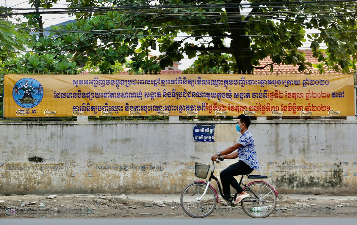 A man rides a bicycle past a banner asking people to confirm their personal information and register to vote ahead of the 2022 commune election, October 4, 2021. CamboJA/ Panha Chhorpoan
